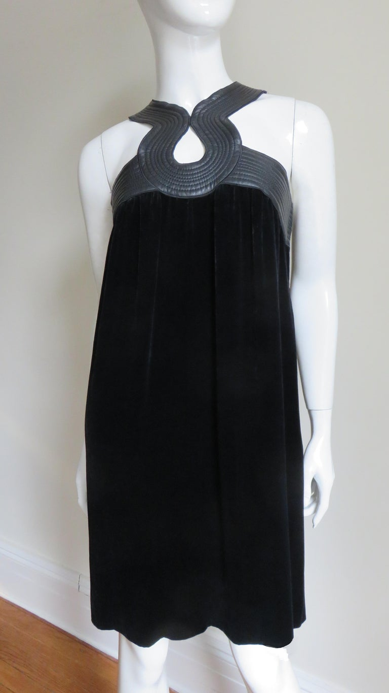 A fabulous black silk velvet dress from Jean Paul Gaultier.  It has incredible leather trim with rows of top stitiching around top of the dress and neck creating circle cut outs in the front and mid back.  It is unlined and closes on the side with