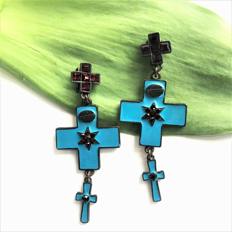 Very nice ear clips from Gaultiere consisting of 3 crosses. The top cross with red rhinestones The Maltese cross hangs in blue enamel, in the middle a star with red rhinestones and a mini cross with red rhinestones. Signed on the front and on the