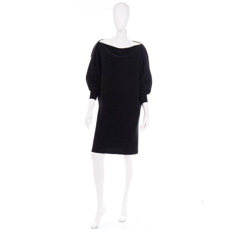 This vintage Jean Paul Gaultier black sparkle knit dress has a metal zipper that starts at the base of the cuffs and wraps around the arms, shoulders, and neck opening. The neckline is completely adjustable with the zippers. The sparkle starts to