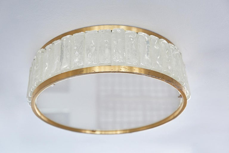 Stunning circular flush mount by Jean Perzel. Beautifully constructed light made up of solid brass trim, thick solid individual side glass pieces and an opaque glass diffuser. Nice patina and age to brass.  Two smaller flush mounts also available