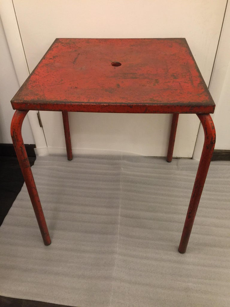 Beautifully distressed through the years of being outside and earning a rich patina. This Jean Prouvé attributed table has a deep classic red paint which is classic Prouvé. This table will make a great side table or game table - just stunning!