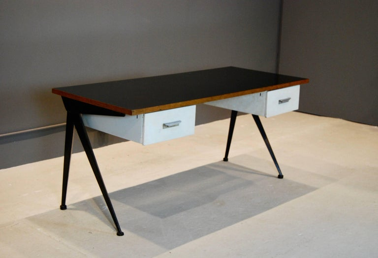 Iconic Compas desk, created by Jean Prouve and manufactured by Atelier Prouve in the 1950s. Compas- shaped legs support black laminated wood top and two steel drawers. This desk is in all original condition. Great style and function.