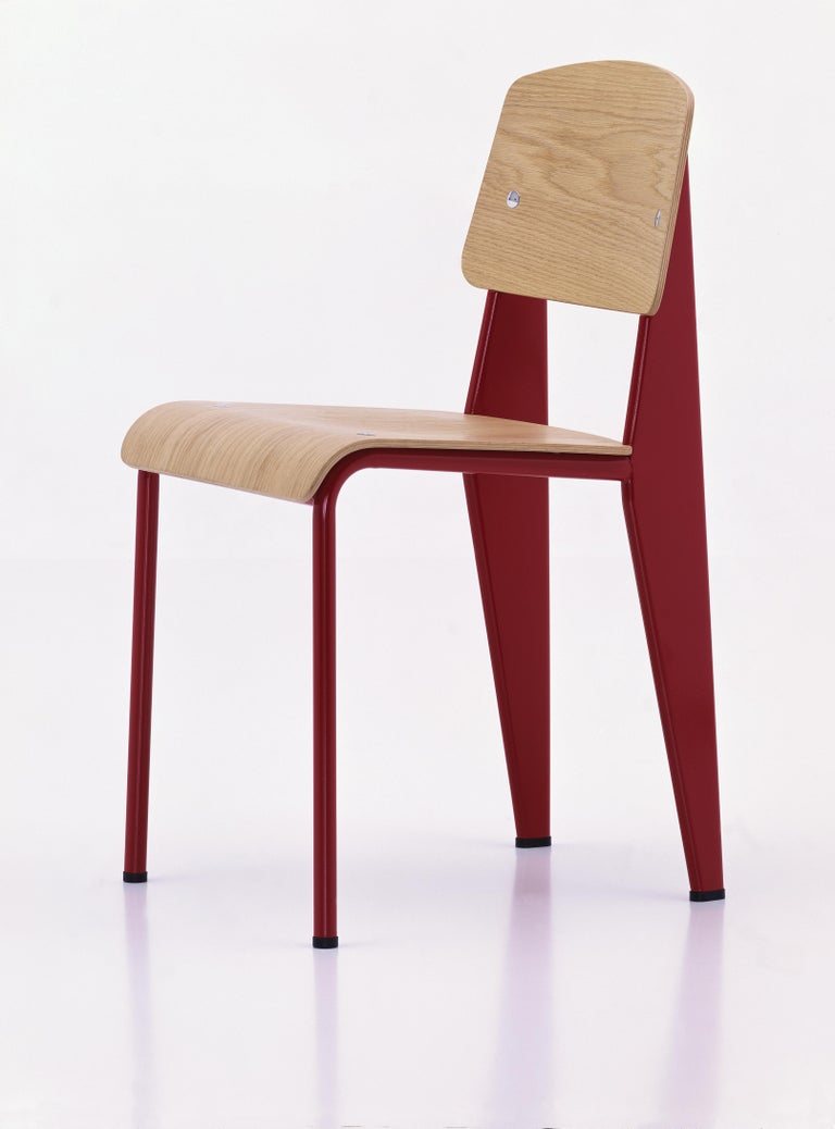 Jean Prouvé Standard chair in natural oak and red metal for Vitra. The Standard chair is an early masterpiece by the French designer and engineer Jean Prouvé. Originally designed in 1934, the Standard evolved into one of the most famous classics of