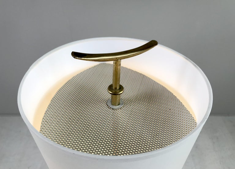 Jean Rispal, Japanese tripod floor lamp in blackened wood, circular tablet in oiled Okumé plywood, France 1950. The inverted cone reflector contains two light bulbs, surmounted by a perforated white lacquered metal plate fixed by a brass
