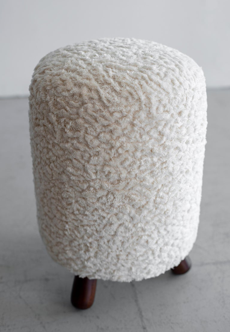 Great shaped stools with Royere style tripod legs. Reupholstered in textured wooly boucle fabric.