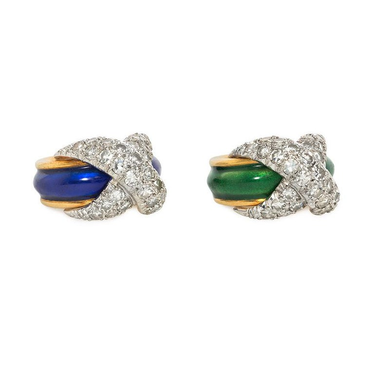 A pair of mid-century gold, enamel, and diamond pinkie rings of band design, comprising one in green enamel and one in blue, with diamond X-form overlays, in 18k gold.  Jean Schlumberger, France.  Original paired box.  Atw single cut diamonds in