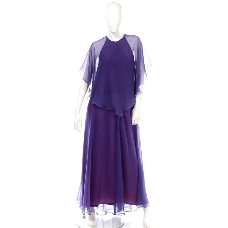 This dreamy vintage Jean Varon evening dress has a sleeveless shape with a chiffon overlay cape that covers the shoulders and creates a sheer sleeve. This dress has a beautiful plum purple lining with a true purple sheer layer that gives this