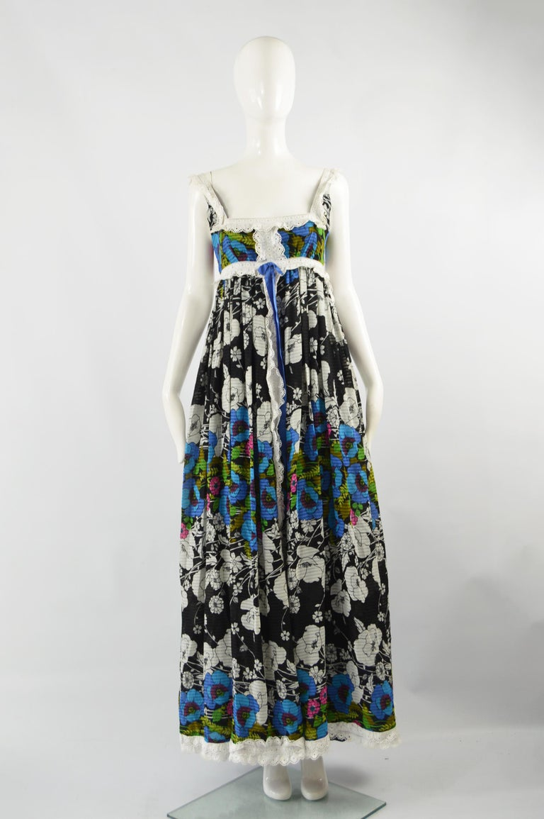 A beautiful vintage sleeveless maxi dress from the 70s by iconic British fashion designer, Jean Varon. In a black, blue and green floral print fabric with a broderie anglaise trim. Perfect for spring and summer.  Size: Not indicated; fits like a