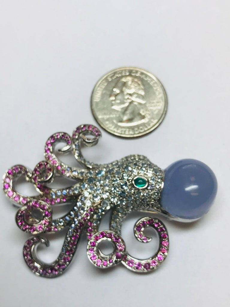This whimsical 18k white gold Jean Vitau Octopus brooch combines 4.00 carats of light blue Aquamarines in the body with 2.75 carats of Pink Sapphire and a beautiful cabochon Chalcedony, finished off with an emerald eye. So incredibly manufactured
