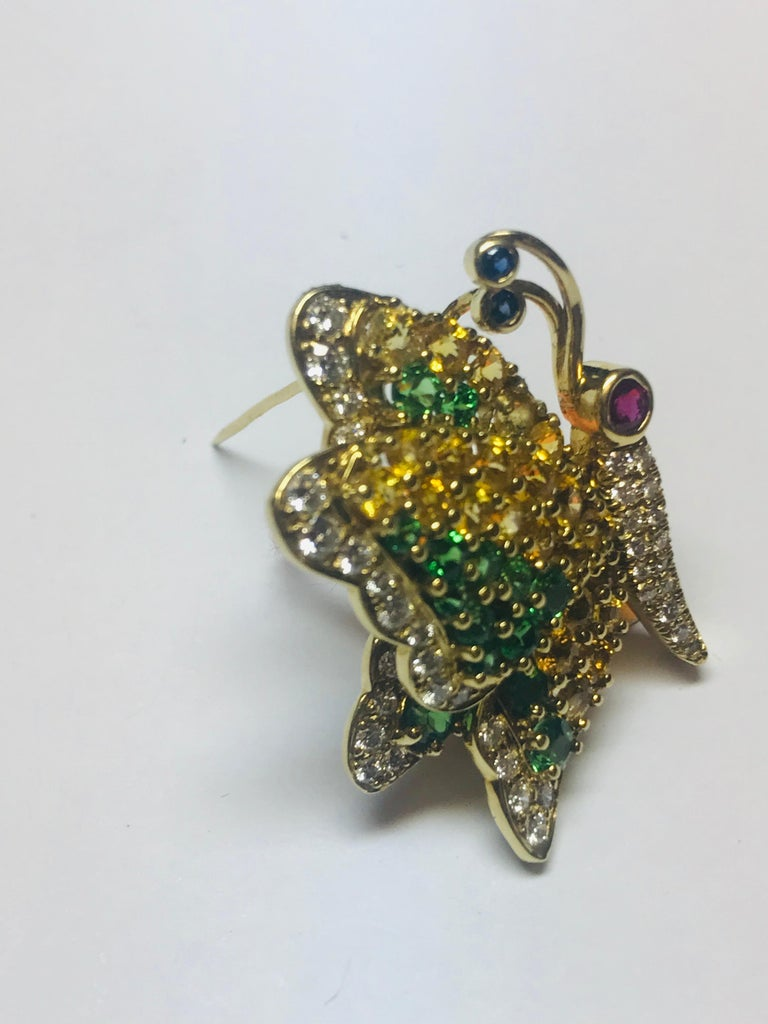 This uniquely designed profile butterfly brooch by Jean Vitau combines 2.70 carats of Yellow Sapphire, 1.70 carats of very rare Tsavorite Garnets and .64 carats of Diamonds, all of gem quality. There is also a Ruby eye and Blue Sapphire in the
