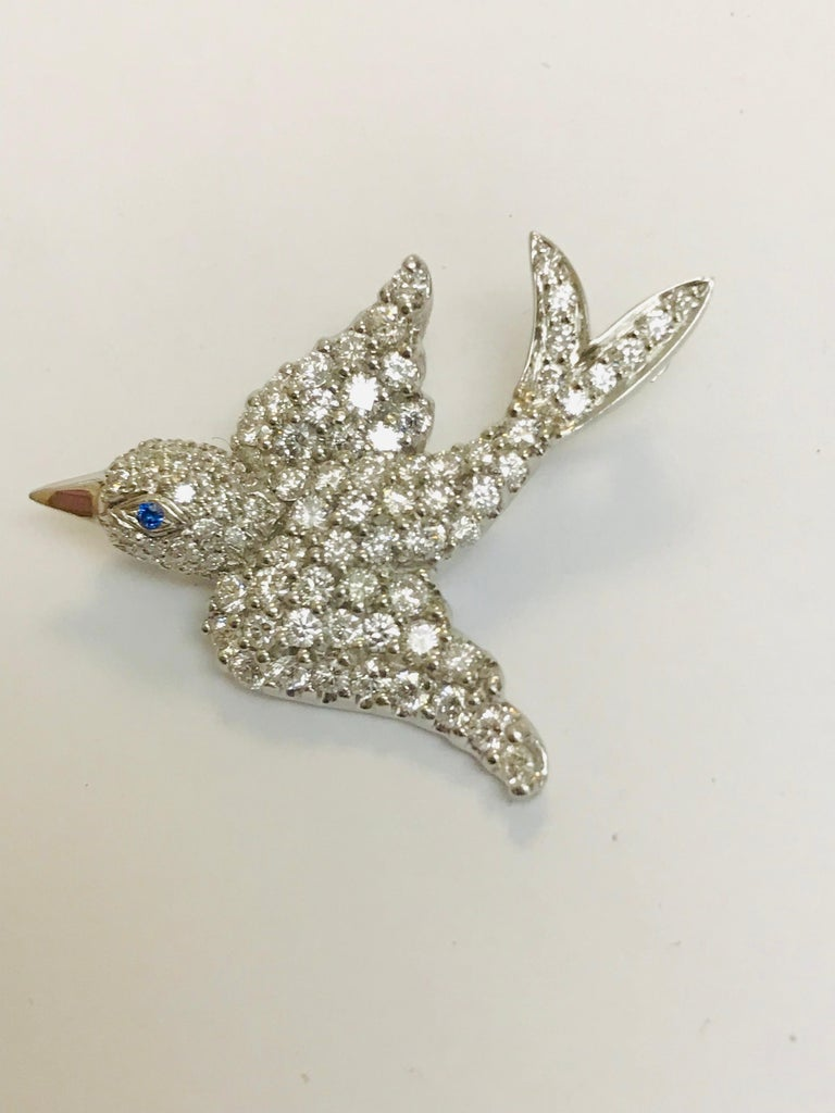 This bird in flight brooch, designed and created by Jean Vitau, is beautifully crafted in Platinum with 2.30 carats of g+ color VVS clarity diamonds. She has a light blue Sapphire for her eye. This brooch can be altered to be worn as a pendant as