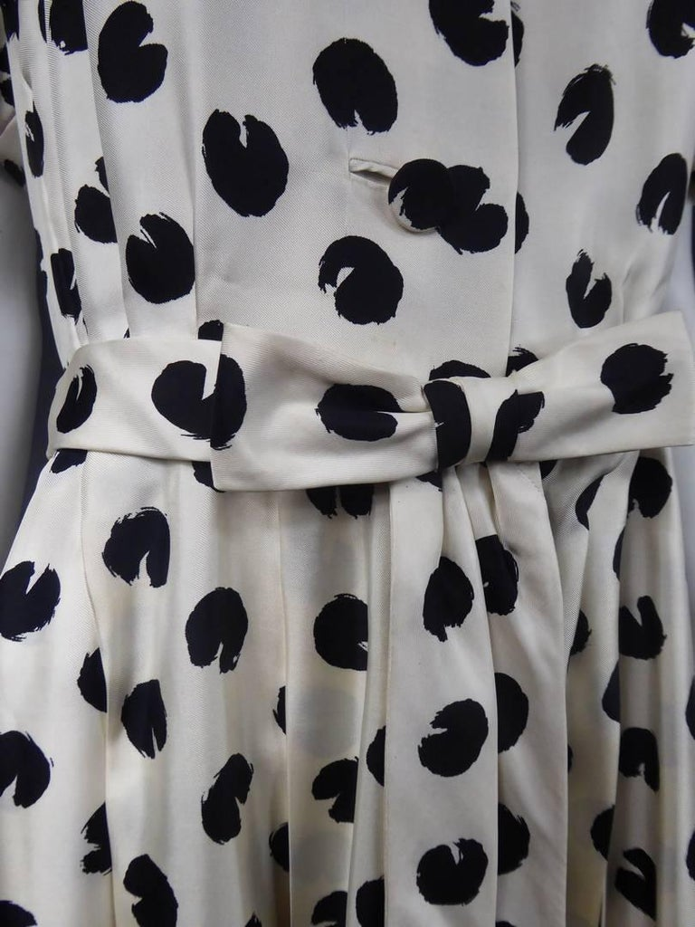 Circa 1960  France  Silk dress with black polka dots on a white background accompanied by a similar bow belt and fringed pans, by the Jeanne Lanvin House directed by Antonio Castillo and dating from the 1960s. Front closure by three buttons in the