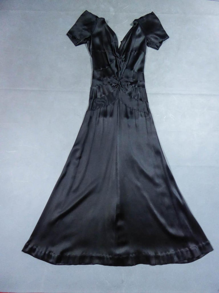 Circa 1935 France  Evening dress in Duchess black satin from the famous french Couture designer house Jeanne Paquin and dating back to the 1930s. Typical cut in bias of this period by hand-stitched panels celebrating a slender and glamorous