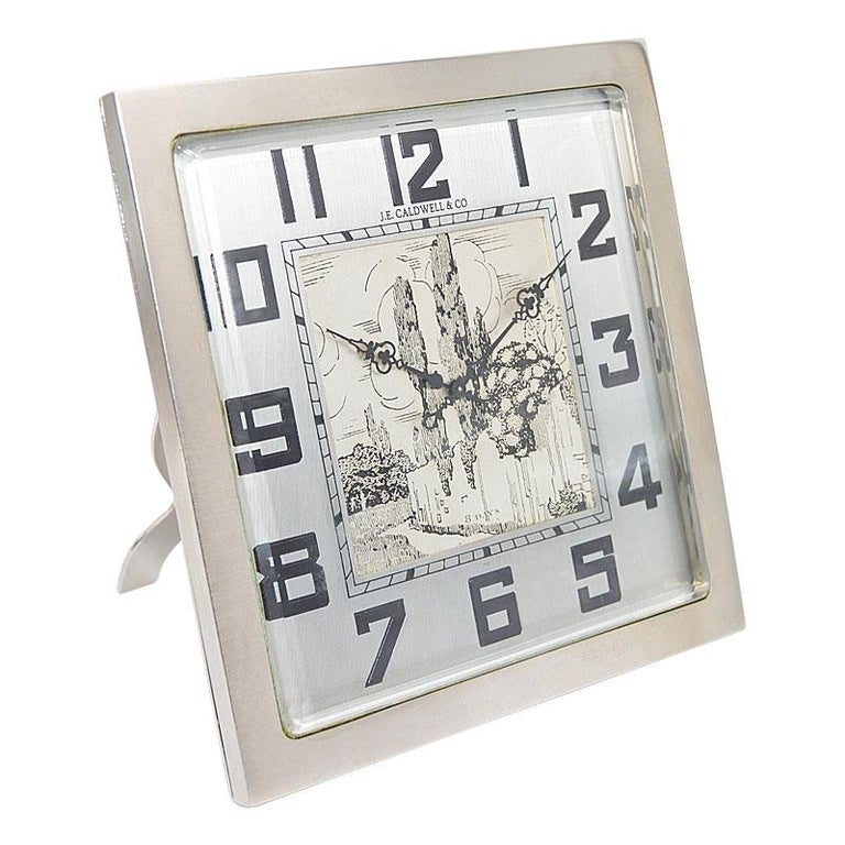 FACTORY / HOUSE: J.E.Caldwell, Philadelphia STYLE / REFERENCE: Art Deco Desk Clock METAL / MATERIAL: Nickel Finish CIRCA / YEAR: 1930's DIMENSIONS / SIZE: 8 Inch Square MOVEMENT / CALIBER: Manual Winding / 15 Jewels / 8 Days DIAL / HANDS: Hand Made
