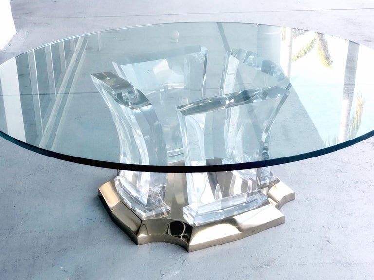 A Jeffrey Bigelow coffee table. the thick, solid and faceted elements rest on a a solid brass base. Round glass top but could use a square or rectangular top.