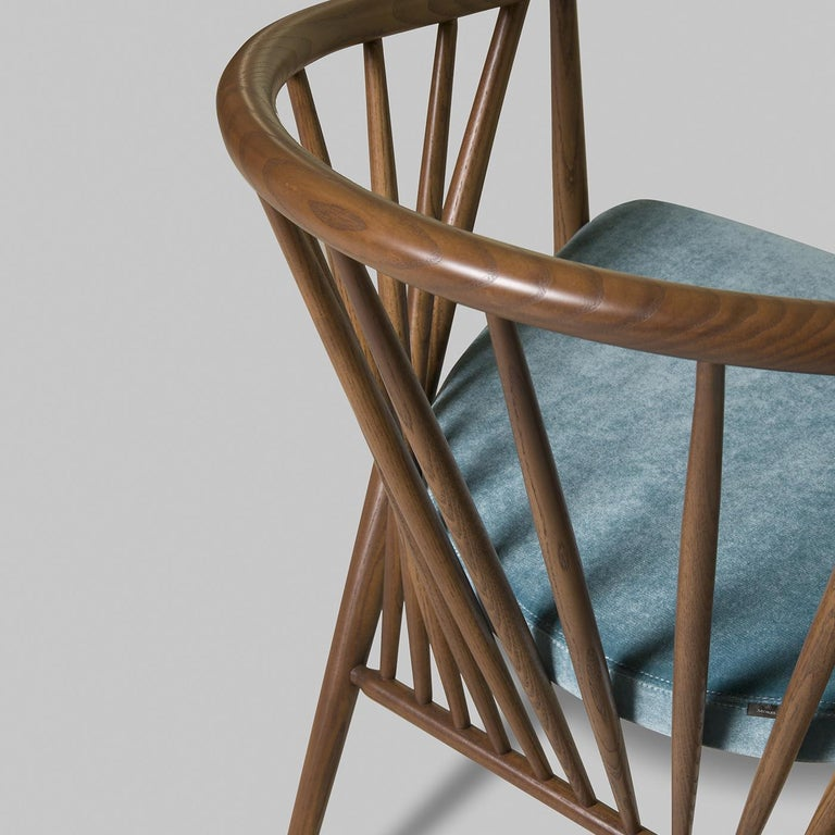 Jenny is an original line of chairs made of solid walnut ash wood with an upholstered blue velvet seat. Thanks to the elegant arrangement of the poles of the curved back, the structure is particularly light and airy, perfect to give a touch of