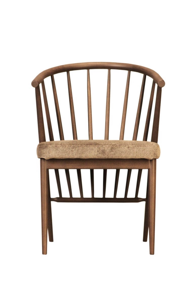 Jenny contemporary upholstered chair in hand-turned ashwood. The curved backrest is made of a raw of ash poles fixed at different angles.