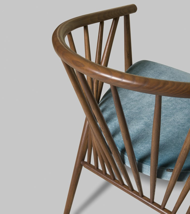 Jenny contemporary upholstered easy chair in hand turned ashwood. The curved backrest is made of a raw of ash poles fixed at different angles.