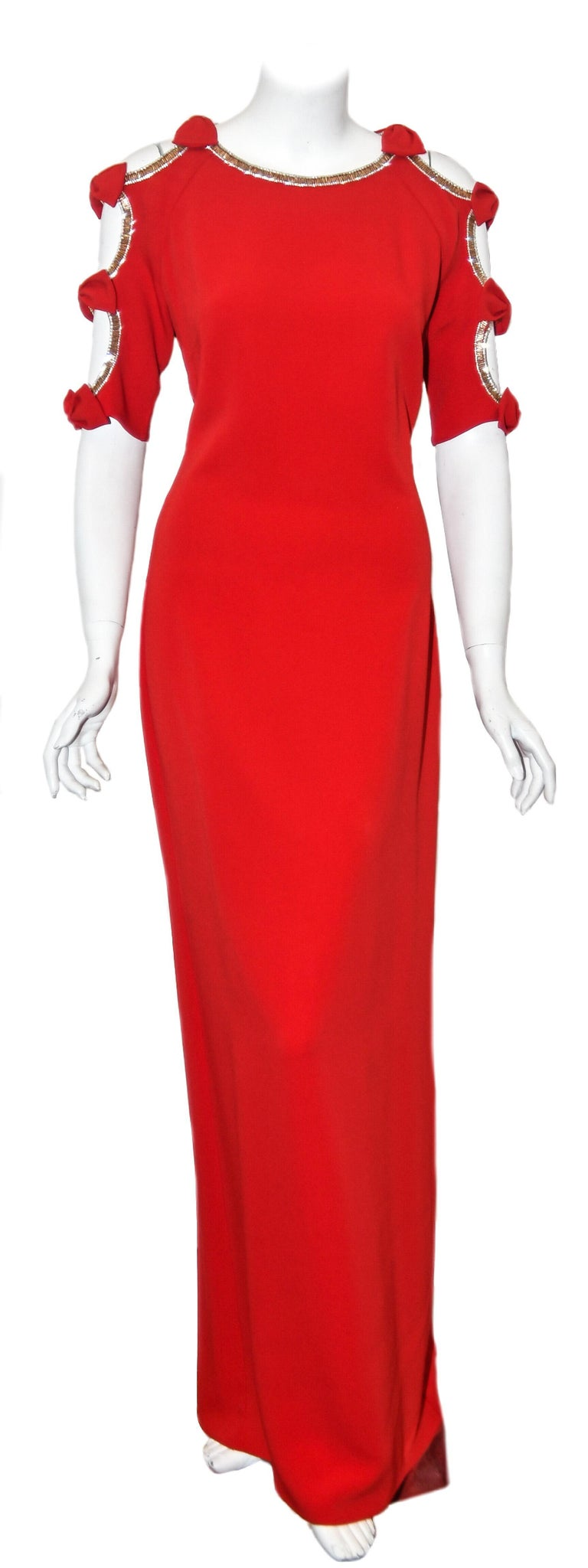 Jenny Packham can almost be classified as the official designer of the royals. This designer has unique and exceptional gowns for all occasions.  This red cold shoulder long evening dress has a beaded trim around neckline, shoulders and sleeves. The