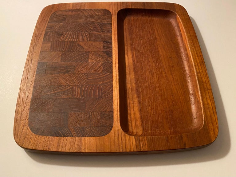 A divided teak wood tray with an end-grain teak cutting surface and a recessed section, designed by Jens H. Quistgaard for Dansk. Branded