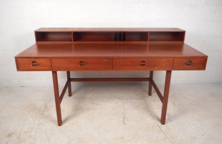 A versatile midcentury desk with plenty of room for storage and a flip top with storage trays and cubbies. This stunning Danish modern desk boasts a rich teak finish, four large drawers, and stretchers along the base for added sturdiness. When the
