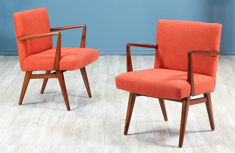 Pair of easy chairs designed by Jens Risom for Knoll Inc. in the United States circa 1950's. These stylish chairs feature a solid walnut wood frame with tapered legs and carved angled arm-rests. The seats have been recently upholstered in a soft