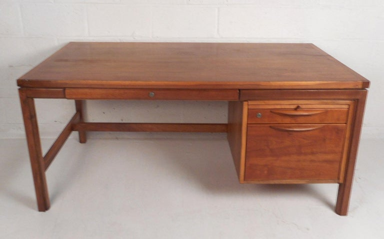 This beautiful Mid-Century Modern desk features three drawers and a pull-out table. A stylish design with plenty of room for storage and plenty of work space. Quality construction with sculpted drawer pulls and a finished back. This newly refinished