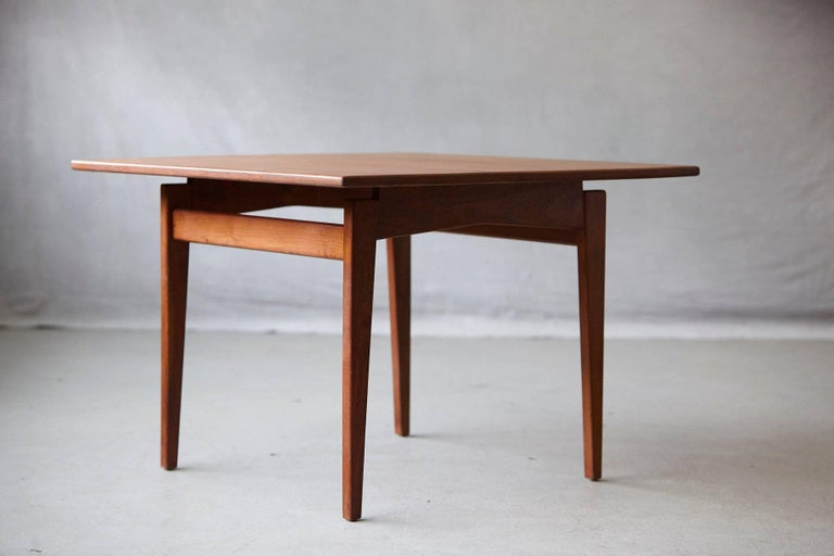 Square coffee or side table with slightly tapered walnut legs and stretchers and a 'floating' square walnut top, designed and manufactured by Jens Risom Design Inc. The table has been lately refinished and is in excellent condition.