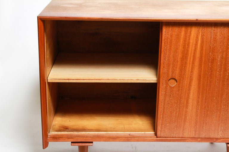 Mid-Century Modern credenza or cabinet designed by Jens Risom in the mid-20th century. The piece has two sliding doors and two interior shelves, one being adjustable. Tapered peg legs. In great vintage condition.