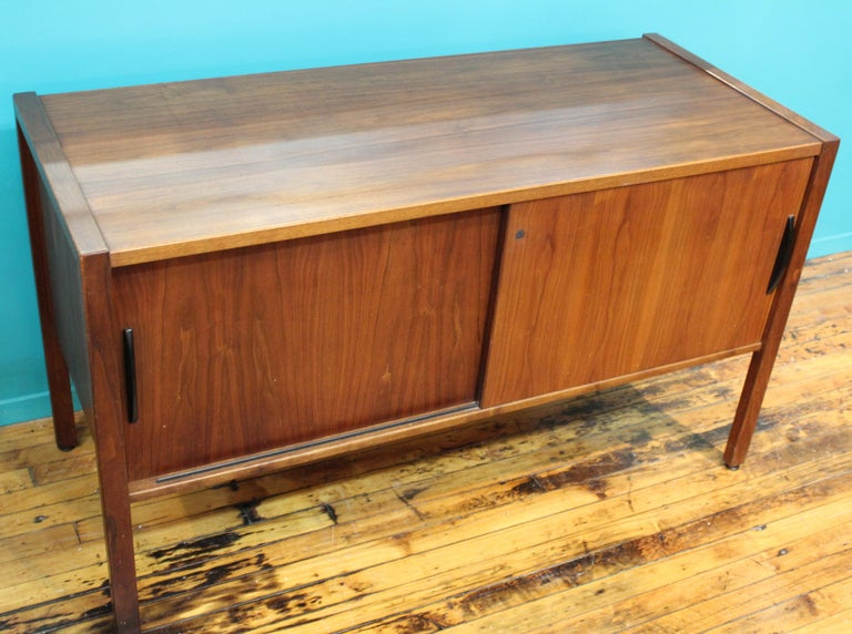 American Mid-Century Modern credenza in teak wood, designed by Jens Risom in the 1970s. The piece has 2 sliding doors and is in great vintage condition with very minor age-appropriate wear.