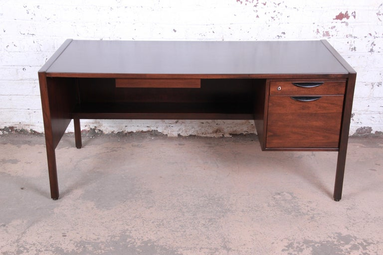 An exceptional Mid-Century Modern walnut executive desk designed by Jens Risom. The desk features gorgeous walnut wood grain and sleek Minimalist design. It offers good storage with three drawers. The desk is finished on all sides and could be used