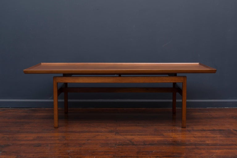 Early Jens Risom design mid century walnut coffee table. Elegant sculpted trims on top with a simple floating base, newly refinished.