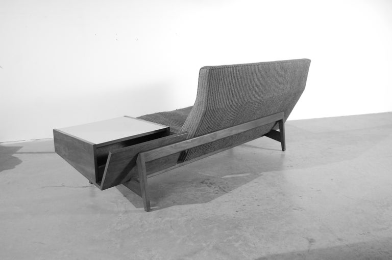 Jens Risom sofa, circa 1955, floating on a walnut frame, with a built in cantilevered storage table with magazine rack and cubbyhole to rear, and storage compartment to front. Please note: This sofa is being offered in