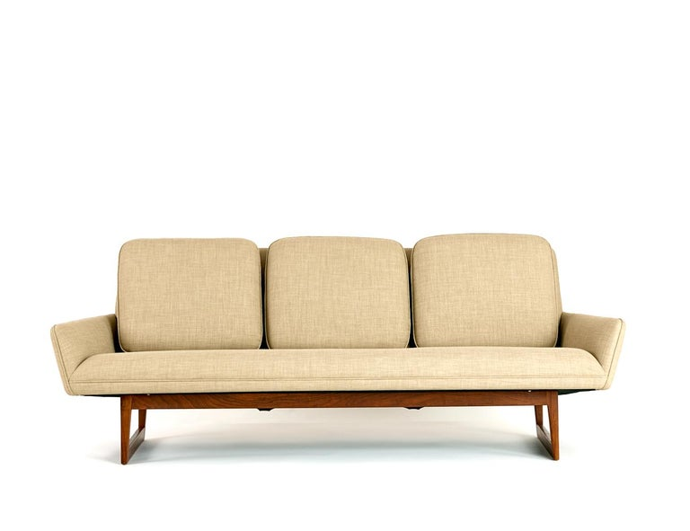 Pair of Jens Risom Sofas  USA Designed and made in the 1960s  Original teak frames with new upholstery and three back seat cushions