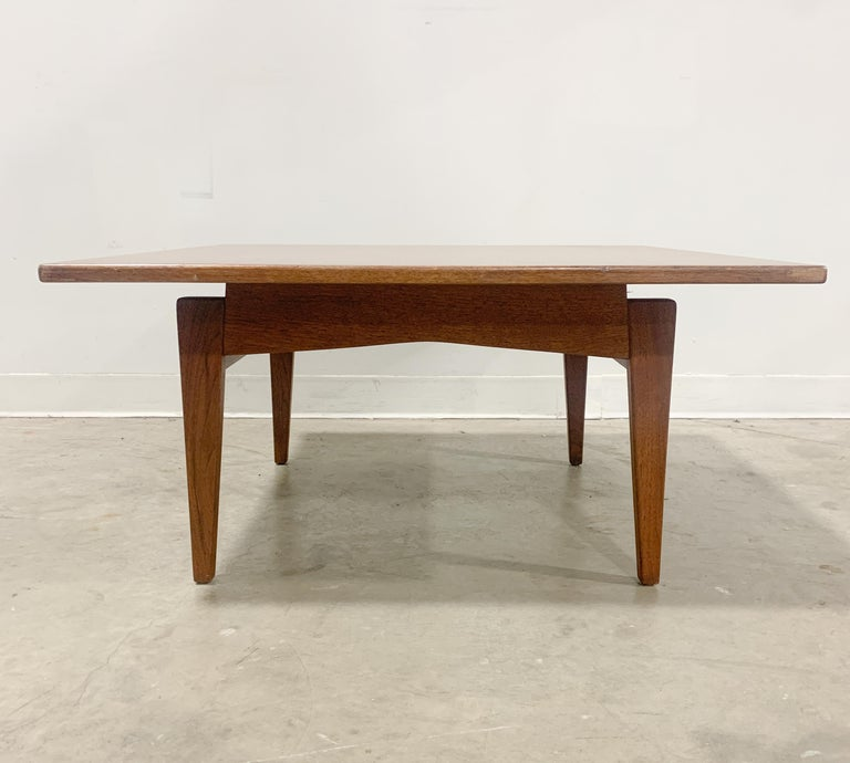 Beautiful solid walnut table designed by Jens Risom for his own company. Distinctive leg design and floating top make this table an eyecatcher. Label not present but you can see where a paper label was adhered underneath, excellent