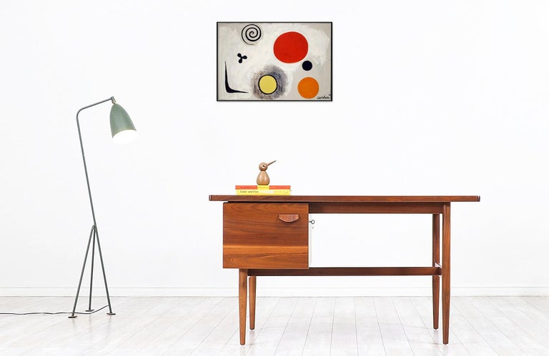 Elegant modern writing desk designed by Jens Risom for Jens Risom Inc. in the United States circa the 1950s. This stylish desk features a walnut wood frame and a file cabinet on the right side for ample storage space. The drawer has a sculpted