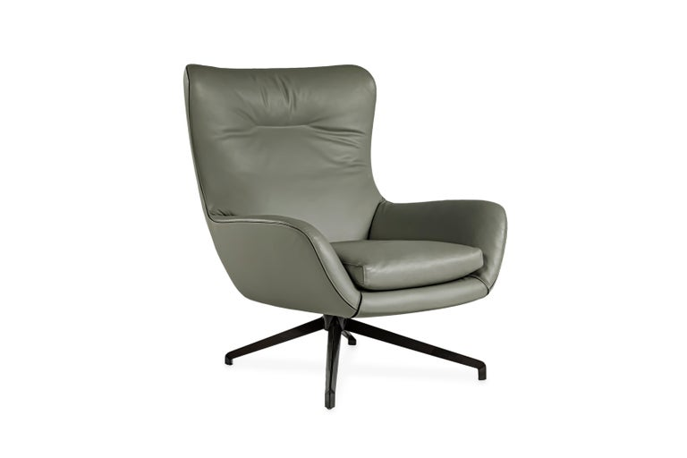 A winged lounge chair upholstered in gray leather, with black fabric piping. The armchair sits on an aluminum base with a pewter finish.