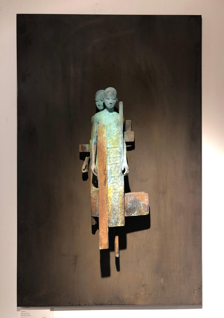 This bronze and steel wall sculpture contains two abstracted figures whose bodies are intertwined and bound together inside a cocoon of geometric and organic shapes.  The combination of matte rust and verdigris bronze emphasize the depth of the