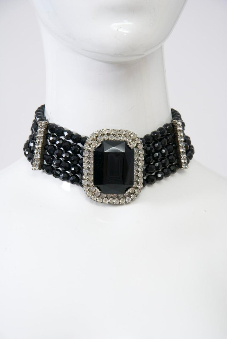 """C.1970s wide choker composed of five strands of faceted black glass beads accented by vertical rhinestone bars at each side and centering a large rectangular black stone surrounded by rhinestones. Adjustable chain closure expands from 12""""-15.5"""";"""
