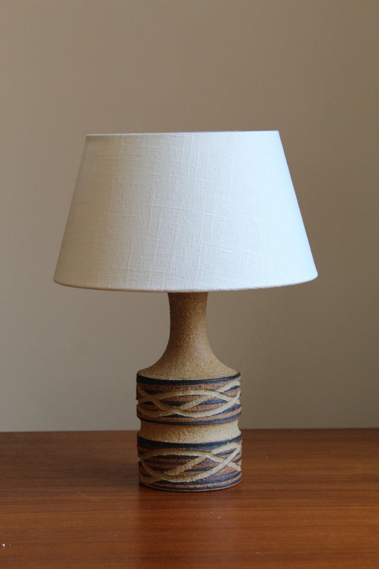 A stoneware lamp, produced by Jette Hellerøe, Denmark 1950, signed.  Other ceramicists of the period include Axel Salto, Wilhelm Kåge, Arne Bang, Claude Connover, and Carl-Harry Stålhane.