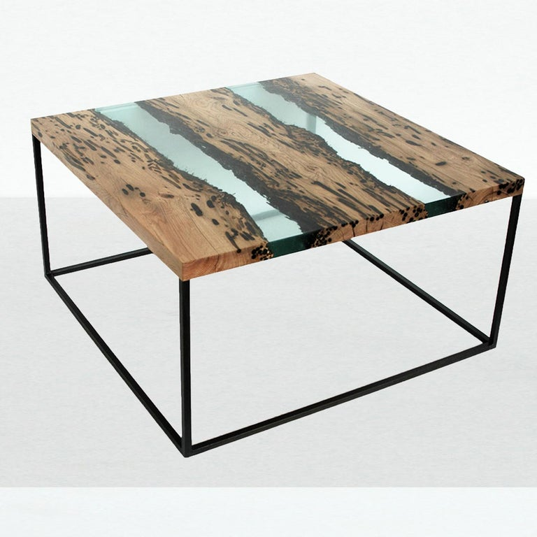 This elegant coffee table has a fine steel structure on which the top rests, creating a floating space where wood and water coexist. The reclaimed vintage oak wood of the many poles of the Venetian laguna is preserved in a special transparent resin