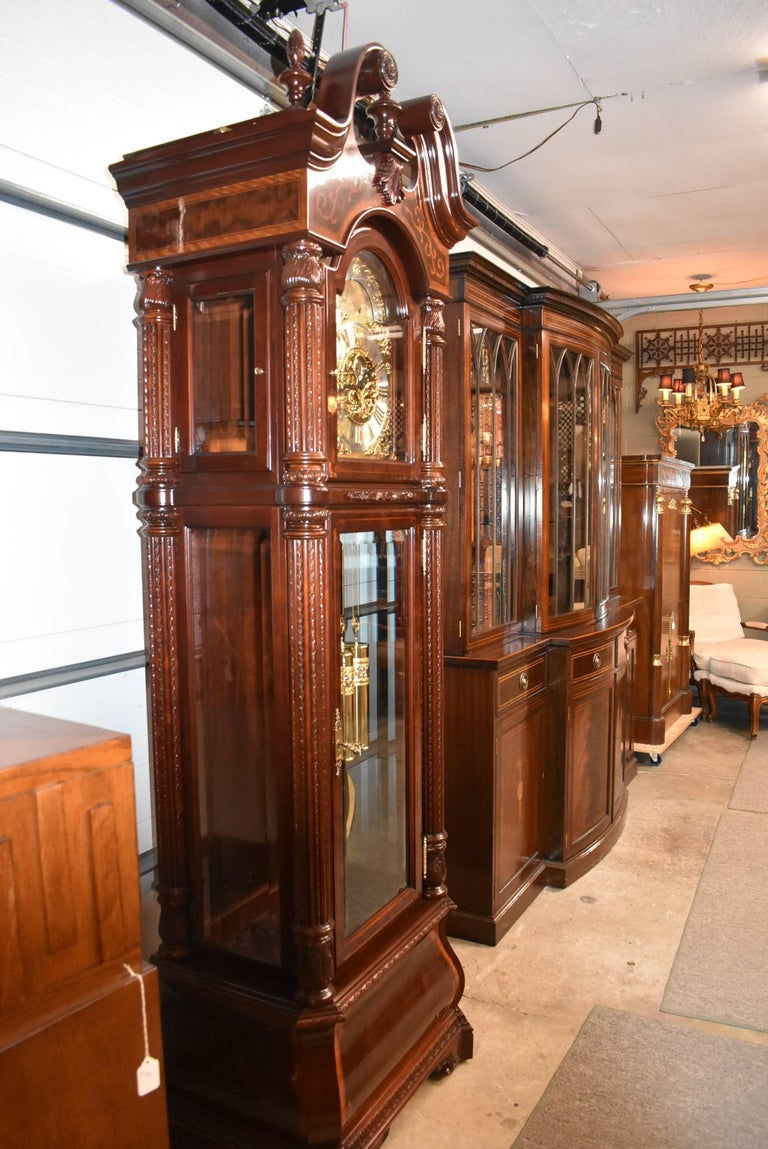 A stunning grandfather clock by Howard Miller, The J.H. Miller, 0611-030. This clock is 8 years old. This beautiful piece was finished in Windsor Cherry. The swan neck pediment is crowned with three carved finials, two carved rosettes and a carved