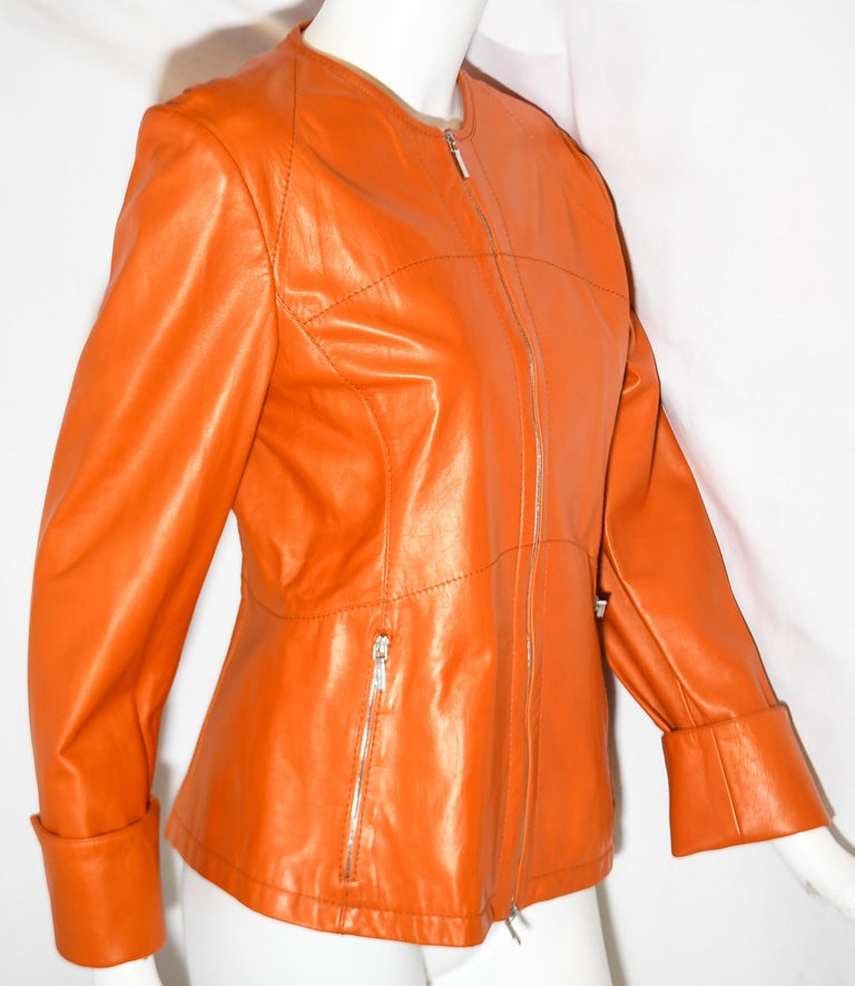 Jil Sander orange leather jacket is fit to the body and includes one silver tone front zipper for closure and two silver tone side zippers one for each pocket.  This jacket is expertly created in Italy.  Jacket is lined in orange fabric.  This round