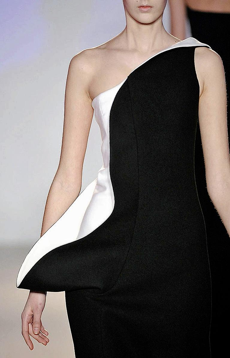 Stunning Jil Sander in a black and white palette featuring a one shoulder sculptural silhouette. Boasts a sculpted section from the shoulder to hip that stylishly hugs the side of upper body.  Fully lined with a side zip closure.  A timeless classic