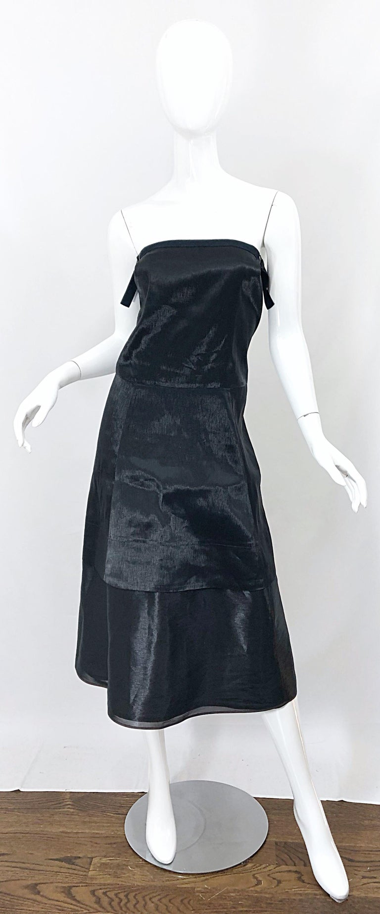 Chic minimalist at its best! This 1990s JIL SANDER strapless dress is so much more than a classic little black dress. You will find yourself wondering if you are wearing a black or gunmetal dress. Beautiful metallic 'wet look' fabric gives off the