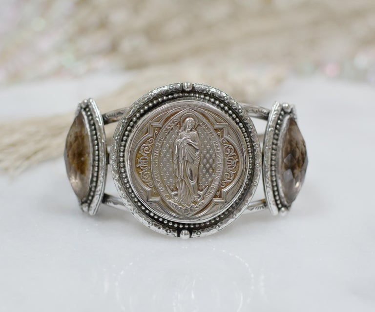 This one of a kind sterling silver Jill Garber cuff bracelet features a fine original antique nineteenth century French Sacred Heart Medal depicting Saint Mary, by engraver Ludovic Penin (1830 - 1868). This master French engraver was accorded the
