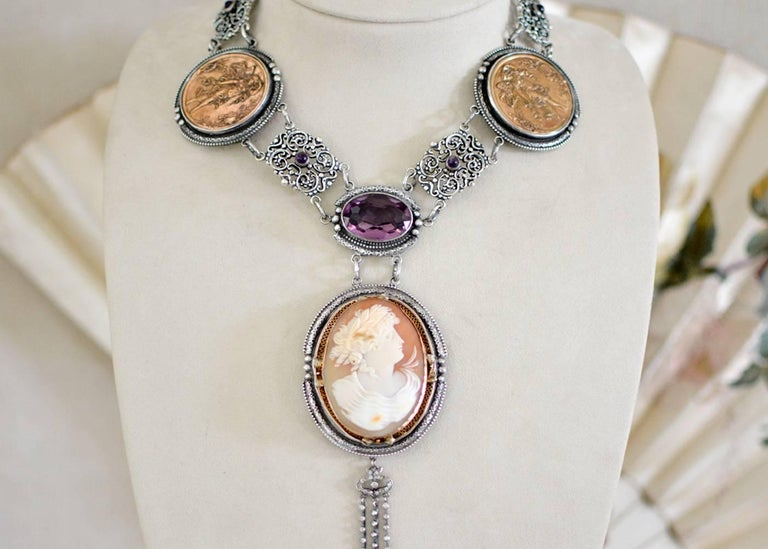 An old cut, 46 carat natural Amethyst set within an elongated oval frame holds a very finely carved mid nineteenth century cameo depicting a Greek Goddess. The original delicate filigree frame of 14 karat gold is mounted within engraved sterling
