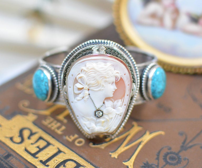 This sterling silver cuff bracelet features an antique period finely hand carved cameo depicting a lovely girl framed within a horseshoe. Wearing a natural diamond necklace, she is mounted in a filigree frame of 14 karat white gold, then edged in