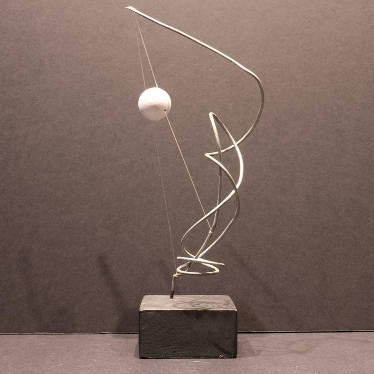 Abstract sculpture of bent wire with a painted wooden sphere suspended by fish line atop a wooden base, created circa 2010. Essentially a maquette, as Hunter always thinks about scaling up to landscape size. Hunter (born 1963) studied advertising