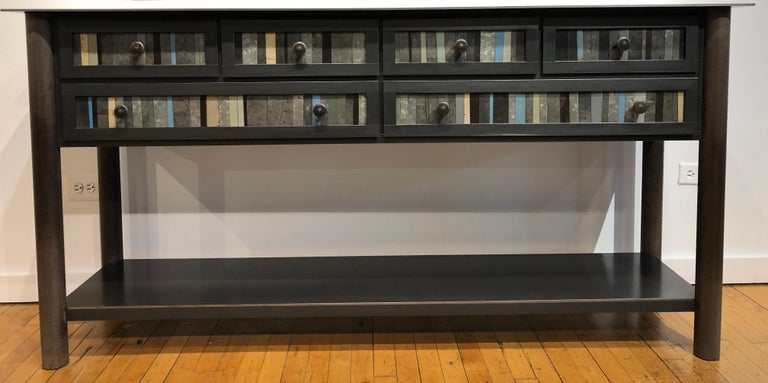 This modern six-drawer counter is made from hot roll blue steel with the front panel design based on the gees bend quilts. Each panel is unique with the use of galvanized rusted steel that is salvaged. Its rich grey, brown and beige tones enhance